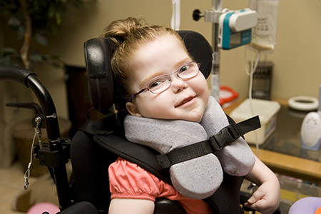 Smiling young girl with cerebral palsy in wheelchair