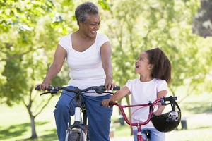 Grandmother biking outdoors with her granddaughter